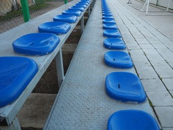 Seats and benches on the sports ground. Plastic blue seats for spectators and fans, empty, no people.