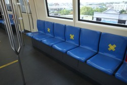 Seats of train,public transportation put yellow cross symbol,signage to remind people not sitting for social distancing to help stop spreading  covid-19 for public health safety. Concept New Normal.