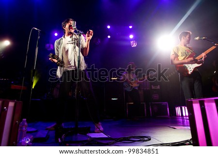 SEATTLE - APRIL 8:  Lead singer Sameer Gadhia of alternative rock band Young the Giant performs on stage at the Moore Theater in Seattle, WA on April 8, 2012. - stock photo