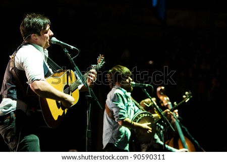 SEATTLE, DECEMBER 7, 2011:  Singer Marcus Mumford of rock band Mumford and Sons performs on stage at Key Arena in Seattle during the Deck the Hall Ball on December 7, 2011. - stock photo