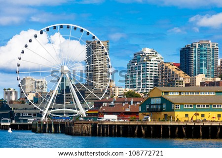 Seattle ferris wheel, waterfront and skyline on a bright sunny day with blue sky and clouds.  View is from the water.  Close up