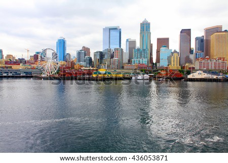 Seattle ferris wheel, waterfront and skyline on a bright sunny day with blue sky and clouds. View is from the water