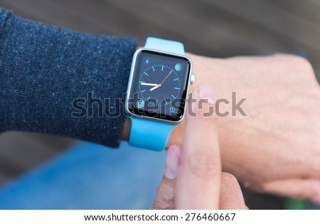 SEATTLE, USA - May 8, 2015: Man Using Watch App on Apple Watch to Check Time.