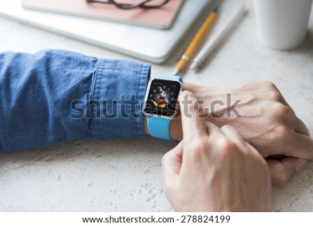 SEATTLE, USA - May 17, 2015: Man Wearing Sport Apple Watch with Blue Rubber Band. Analog Watch Displayed with Dancing Mickey Mouse Background.