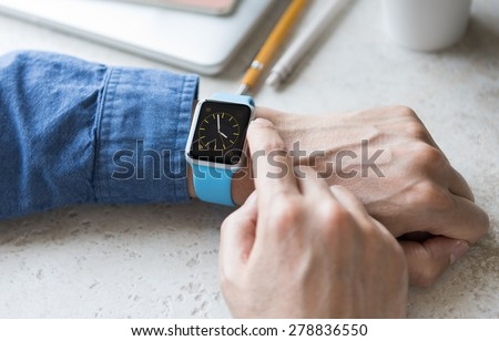 SEATTLE, USA - May 17, 2015: Man Wearing Sport Apple Watch with Blue Rubber Band. Analog Watch View.