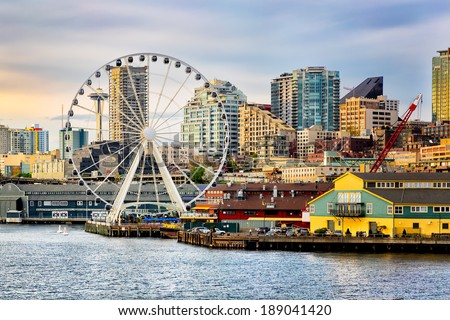Seattle waterfront and skyline, with the Space Needle showing through the spokes of the Great Wheel ferris wheel in the foreground. Colorful image with late afternoon gold light. #189041420