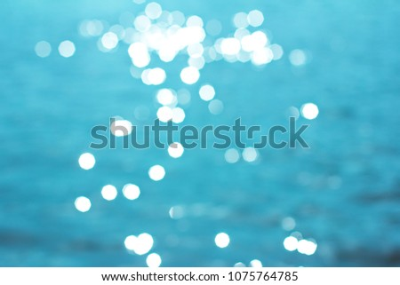 Seawater in sunlight. The photo is in the defocus. Summer background. Sunlight bokeh sparkles deep turquoise water mediterranean sea blurry background