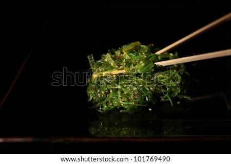 Seaweed salad with chopsticks on a black background