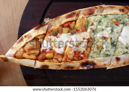 Sebzeli Pide on wooden board in restaurant Stok fotoğraf ©