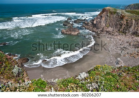 Secluded Beach:  High cliffs form a small, sandy cove on the coast of California.