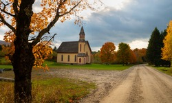 Secluded church in rural northeast United States along a dirt road with no people around in autumn and beautiful fall colors