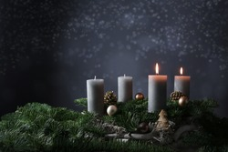 Second advent with two burning candles on fir branches with Christmas decoration against a dark grey background, copy space, selected focus, narrow depth of field