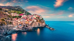 Second city of the Cique Terre sequence of hill cities - Manarola. Colorful spring sunset in Liguria, Italy, Europe. Picturesque seascape of Mediterranean sea. Traveling concept background.