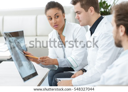 Second opinion. Shot of a female doctor analyzing x-ray scan of the patient with her medical team colleagues at the hospital profession job teamwork communication medicine healthcare concept