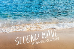 Second wave, Coronavirus, COVID19 text in white on natural background. Concept of fear of second wave coronavirus pandemic outbreak. Real blue sea and golden sand on the beach in Europe.