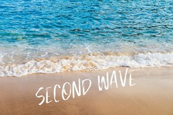 Second wave text in white on natural background. Concept of fear of second wave coronavirus pandemic outbreak. Real blue sea and golden sand on the beach in Europe.