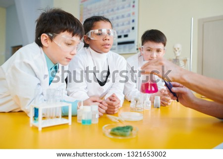 Secondary school students in whitecoats and eyeglasses looking at liquid substance in tube and listening to explanations of teacher