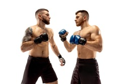 Seconds before war. Two professional fighters posing isolated on white studio background. Couple of fit muscular caucasian athletes or boxers fighting. Sport, competition and human emotions concept.