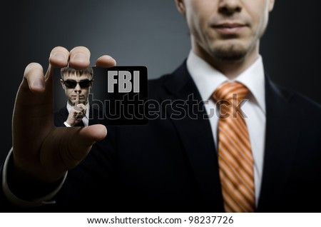 secret agent in black costume and orange necktie reach out on camera and show  visiting card, close up
