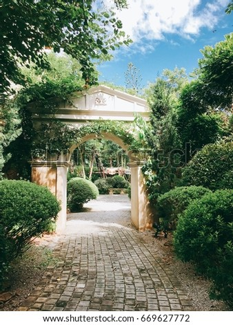 Secret Garden with antique entrance and foot path #669627772