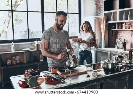 Secret ingredient is love. Beautiful young couple preparing a healthy meal together while spending free time at home