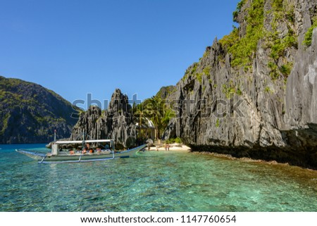 Stock Photo Secret lagoon with crystal clear water surrounded by rocks in El Nido Palawan. Philippine seascape with rocks. Tropical paradise in Asia