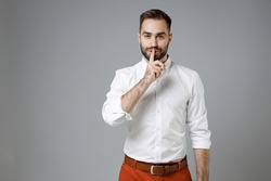 Secret young bearded business man 20s in classic white shirt saying hush be quiet with finger on lips shhh gesture isolated on grey color background studio portrait. Achievement career wealth concept
