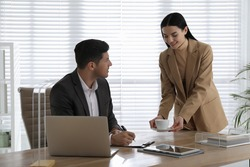 Secretary bringing coffee to her boss in office
