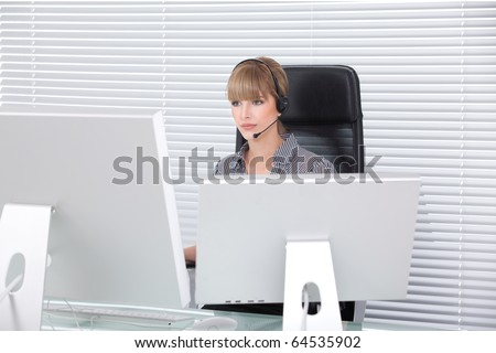 Secretary with headphone and multiple monitors in her clean office