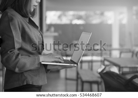 secretary woman typing on her laptop monochrome black and white effect