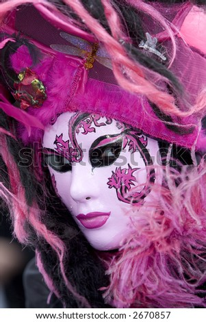 Secretive eyes hidden behind a pink venetian mask - stock photo