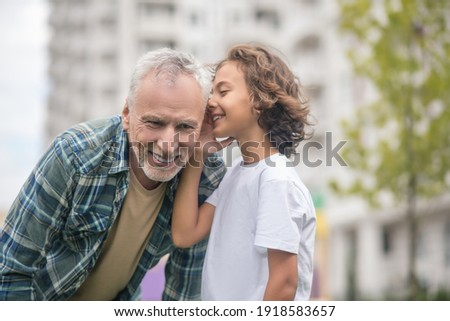 Secrets. Cute dark-haired boy sharing secrets with his dad Photo stock ©