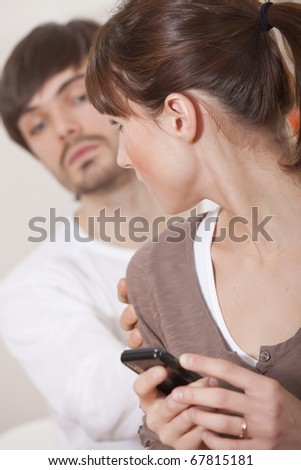 secrets in relationship - woman hiding her mobile phone from curious man - stock photo