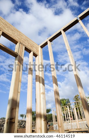 Section of a construction wall framed out in wood against a blue sky. Another framed building can be seen in the background. Vertical shot.