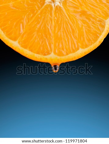 Section of a juicy orange with a drop of juice