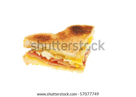 Section of a toasted bacon and egg sandwich on white