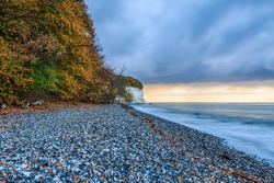 Section of beach on the island of Ruegen. Chalk cliffs with stony coastlines in the morning. Autumn mood with deciduous trees and clouds and calm sea