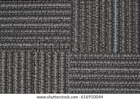 Section of line patterned carpet showing four quarters with the pattern going in a clockwise direction.
