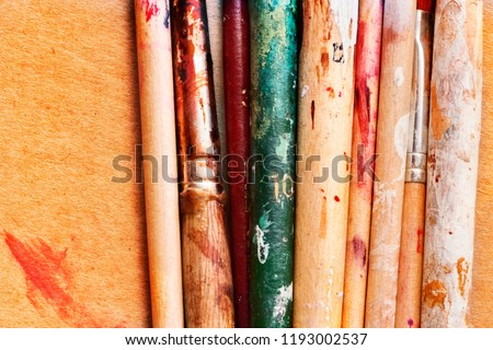 Section of  wooden paintbrushes on a board , splashes of watercolors and paintbrush numbers , top view ,saturated colors #1193002537