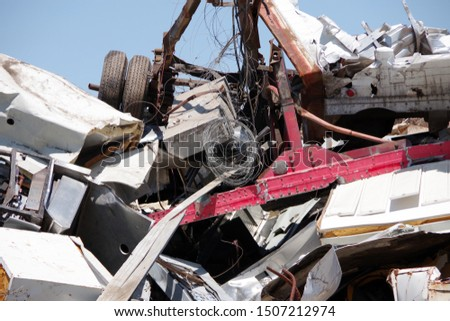 Sectional view into a pile of scrapped vehicles and other materials with blue sky above