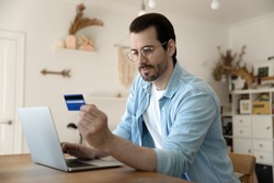 Secure payment. Attentive young businessman operating personal bank account from home computer. Focused male customer input cardholder information online to buy purchase goods services prepay order