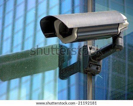 security black camera on glass facade