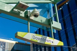 Security camera above downtown sign on public transportation stop. Modern urban cityscape