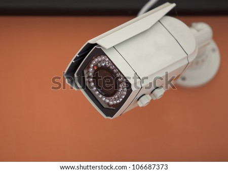 Security Camera,CCTV with orange wall background.