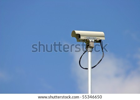 Security camera in cloudy blue sky background.