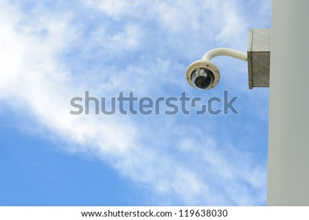 Security camera install corner outside of building with blue sky background.