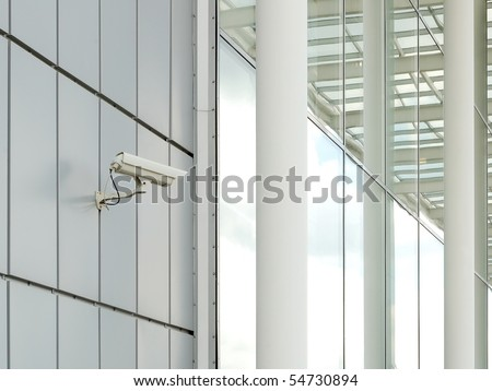 Security camera mounted on the facade of the modern building - stock photo