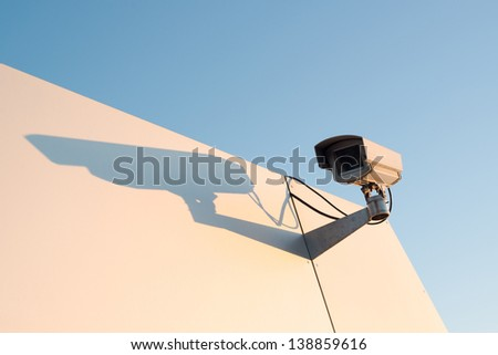 Security camera on a bright metal wall against great blue sky with room for your copytext
