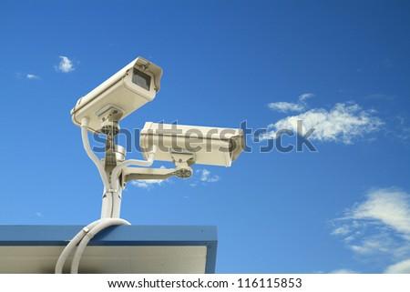 Security camera on blue sky background - stock photo