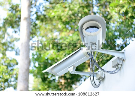 security camera on the fence next to the jungle - stock photo